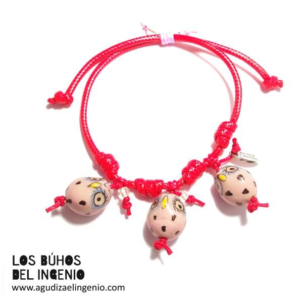 """Pulsera """"Los Búhos del Ingenio"""" tres búhos rosas, cordón rojo"""